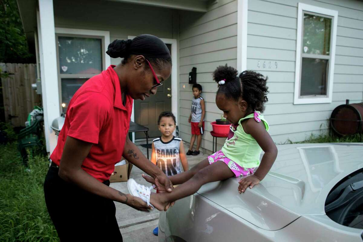 Janelle Ivy, a rent relief recepient, helps her daughter, Chanell Jackson, 2, with her shoes outside her sister's house as she watches her children play Wednesday, May 26, 2021 in Houston. The City of Houston and Harris County launched the joint $159 million rent relief fund in February, marking the largest local investment in aid since the pandemic sparked a housing crisis for renters who saw their incomes plunge when businesses shuttered. Another $93 million in federal rent relief grants is heading to the city's coffers, even as government and nonprofits still are working to distribute about half of an earlier $159 million allotment.