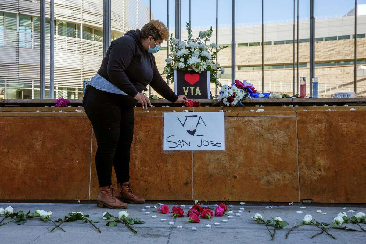Kiana Simmons places flowers down at a vigil at City Hall, Wednesday, May 26, 2021, in San Jose, Calif. A shooting at the VTA Light Rail Facility yard left nine people dead, including the gunman, who was a VTA employee.