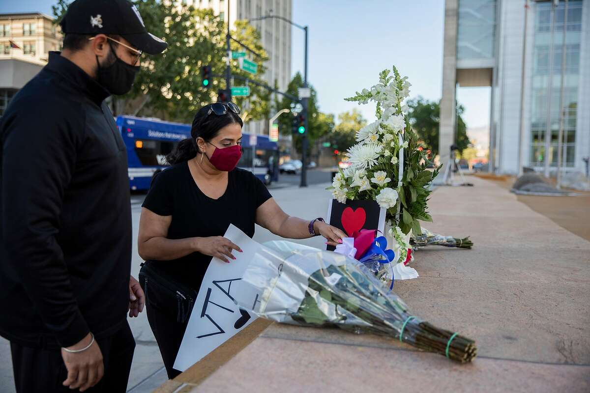 From left: Amar Singh and Jaspreet Kaur put up signs at a vigil at City Hall, Wednesday, May 26, 2021, in San Jose, Calif. A shooting at the VTA Light Rail Facility yard left nine people dead, including the gunman, who was a VTA employee.