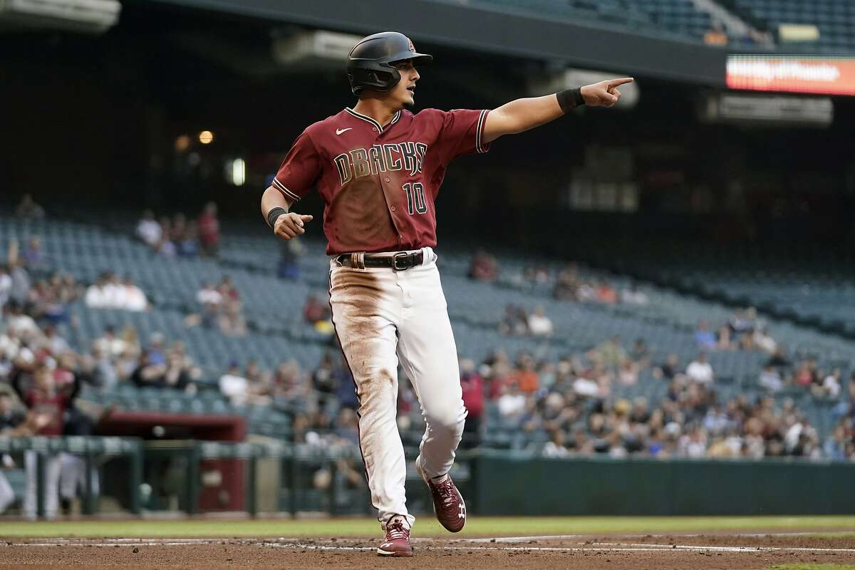 Arizona Diamondbacks' Josh Rojas scores a run while pointing to teammate Ketel Marte, who singled Rojas in during the first inning of a baseball game against the San Francisco Giants on Wednesday, May 26, 2021, in Phoenix. (AP Photo/Ross D. Franklin)