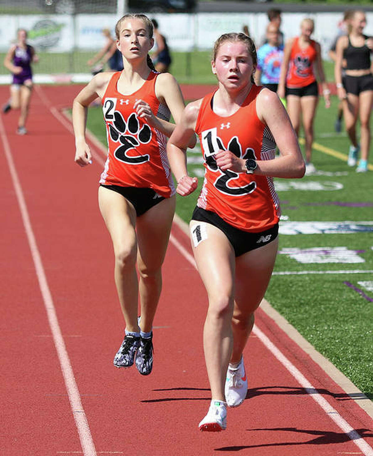 Edwardsville's Riley Knoyle, right, and Maya Lueking compete in the 1,600-meter run at the Southwestern Conference Meet on Wednesday in Collinsville.