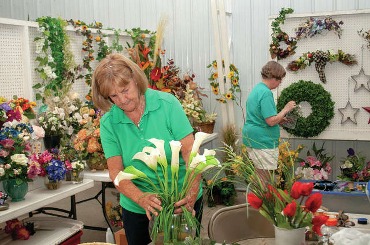 Linda Curtis (foreground), a volunteer with The Salvation Army Women's Auxillary, arranges flowers Wednesday as Martha Vache (back) helps ahead of this weekend's Flea-Esta sale at the Morgan County Fairgrounds on Westgate Avenue. Hours will be from 8 a.m. to 4 p.m. Friday and from 8 a.m. to noon Saturday.