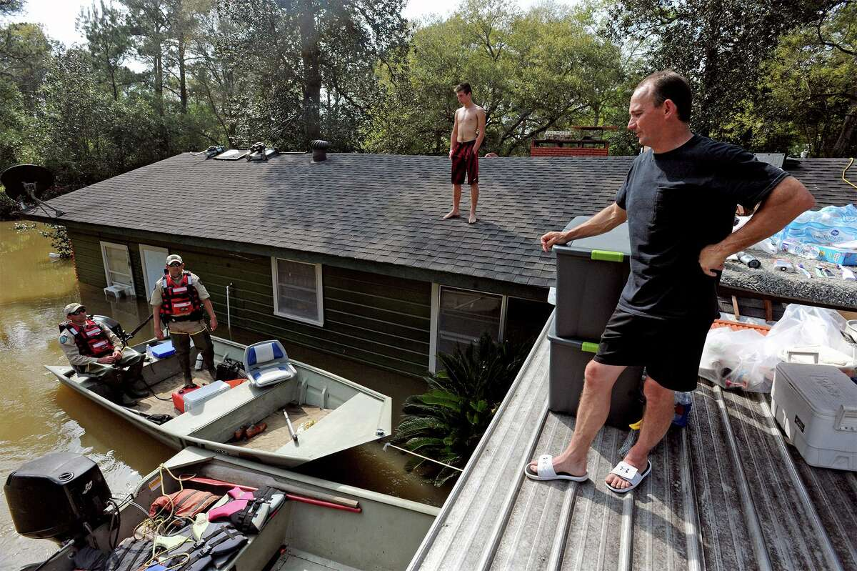 From left, Jamie Holden Sr. and Trent Black, 15, talk to Game Wardens Randy Harper, left, and Chad West from their roof in Deweyville on Wednesday. The family carried many household items and furniture to the roof to prevent evacuation. Items include a washer, dryer, microwave, 65 inch television, grill, generator and an Xbox. Photo taken Wednesday, March 16, 2016 Guiseppe Barranco/The Enterprise