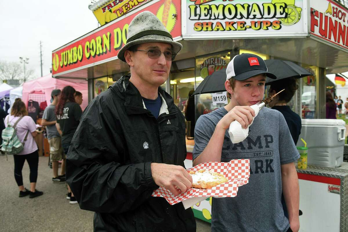 Martin Mohr, left, of Houston, and his son Mike, 15, a sophomore at Houston Memorial High School, enjoy a snack at the Tomball German Heritage Festival at the Tomball Depot on March 30, 2019.
