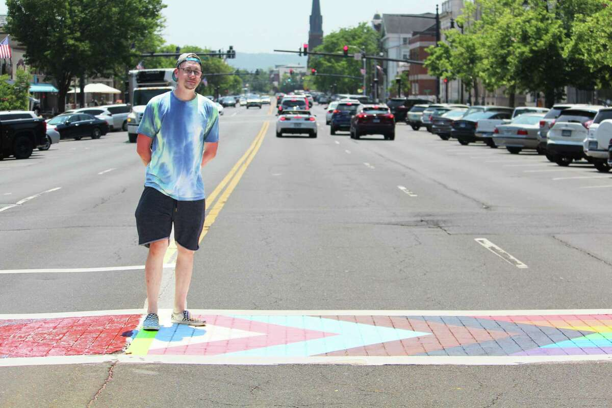 Middletown artist Kenall Soliwoda stands on the faded portion of the Pride crosswalk at 386 Main St. during a break from repainting the mirror-image flag. The original artist, Brian Colbath, gave Soliwoda the renderings he used to design the piece, which is similar to the Pride mural Colbath created in West Hartford center.