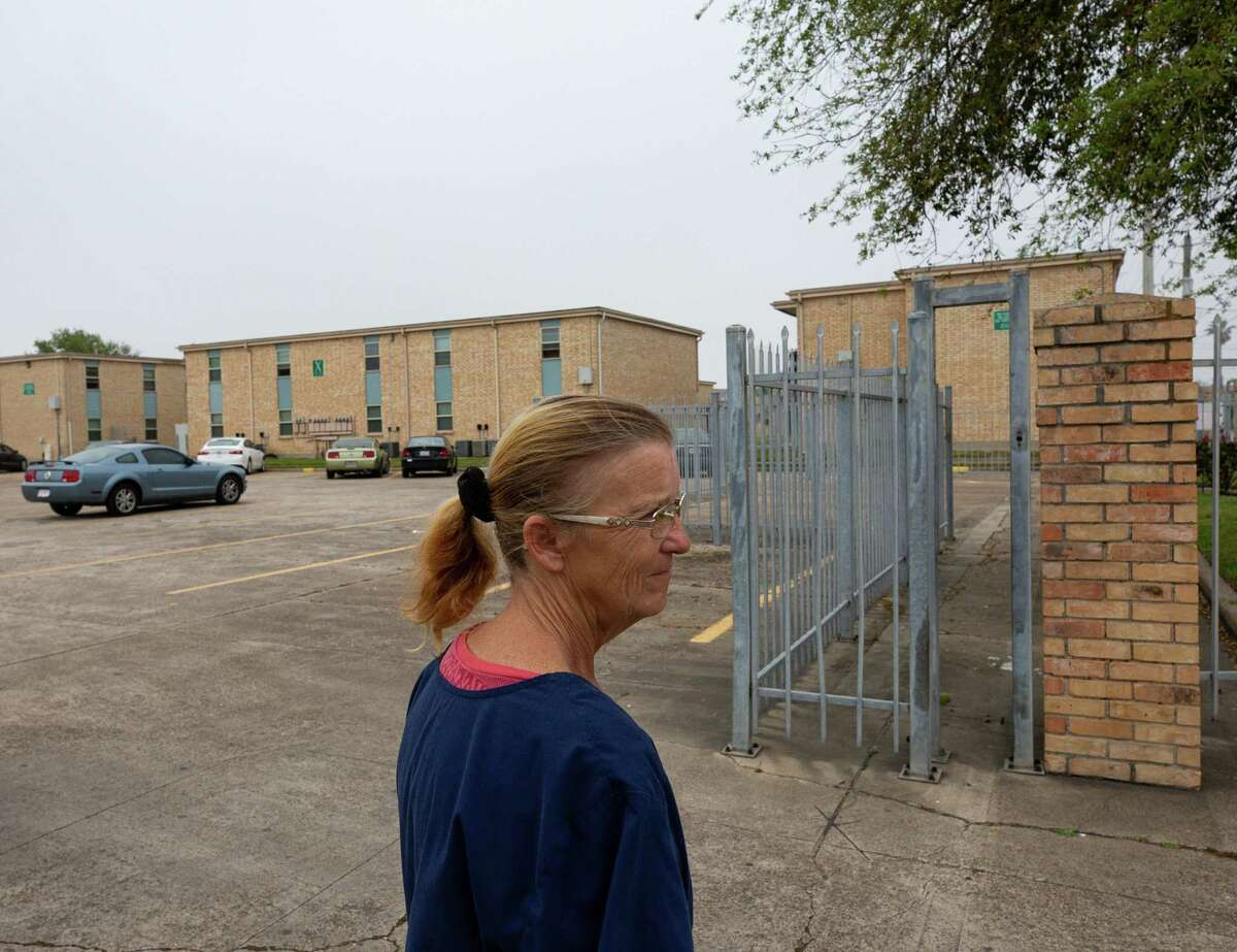 Tina Harris walks through one of the parking lots at Sandpiper Cove apartment complex, where she and her daughter live, on Wednesday, March 11, 2020, in Galveston, Texas. Harris' daughter, Aaliyah Lewis, has asthma, which is heavily triggered by the mold found in their apartment.