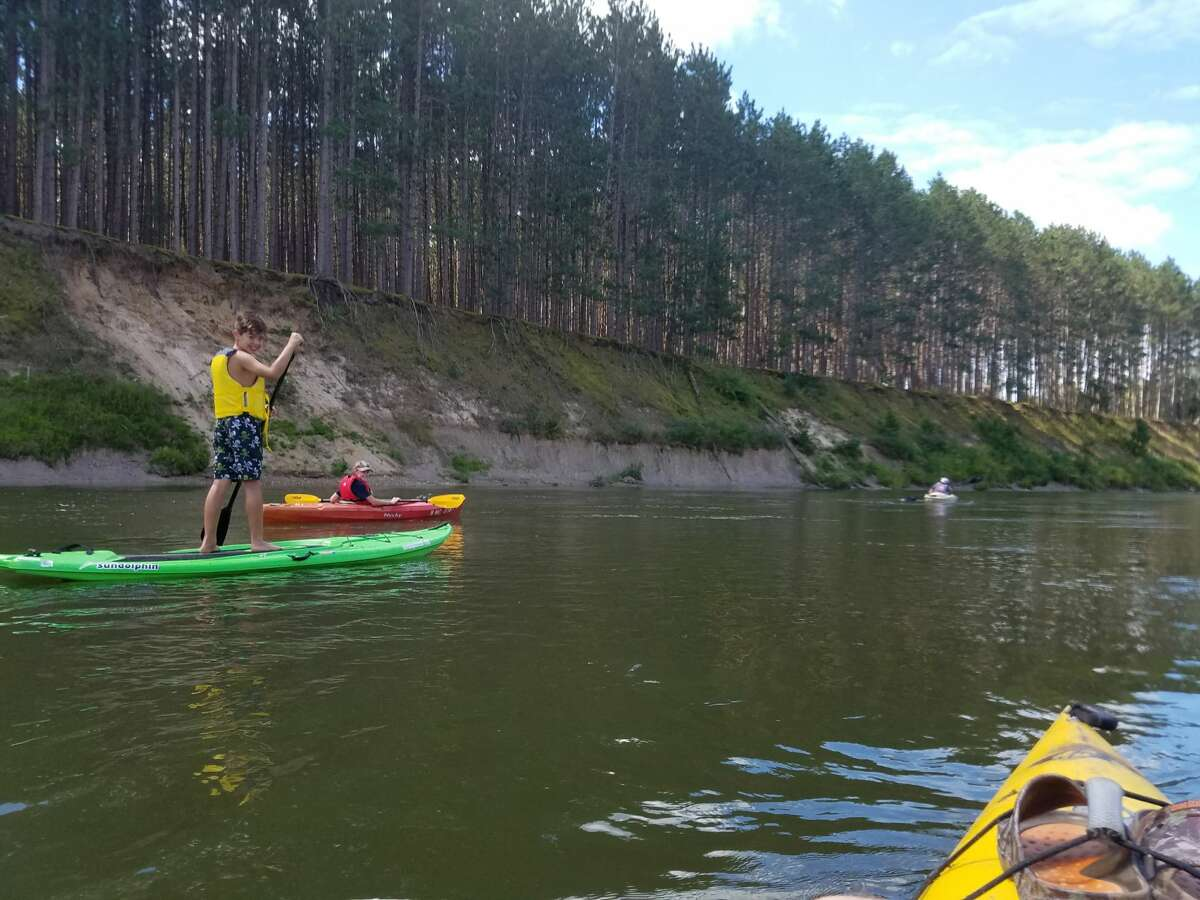 This photo shows a stand-up paddleboard enthusiast on the Big Manistee River while another person in the friend group kayaks last year