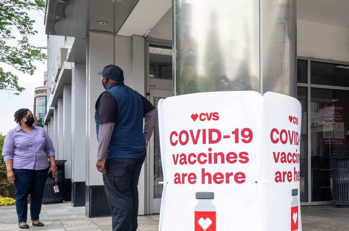 (FILES) In this file photo signs offering Covid-19 vaccinations are seen outside of a CVS pharmacy in Washington, DC on May 7, 2021. - Washington is to lift pandemic restrictions on most businesses and public venues in less than two weeks, with the daily toll of new Covid-19 cases in the US capital at its lowest level in almost a year. As the vaccination drive gathers pace, the city's famed Smithsonian museums and zoo -- as well as shops, restaurants, places of worship and numerous other venues -- will see capacity curbs removed entirely by May 21, 2021. (Photo by MANDEL NGAN / AFP) (Photo by MANDEL NGAN/AFP via Getty Images)