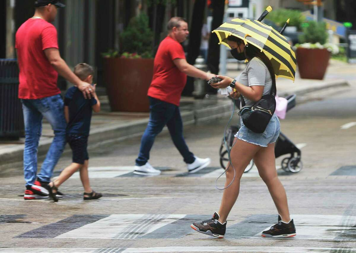 A pedestrian shields herself from rain with an umbrella in downtown San Antonio on Monday, May 24, 2021. Those diligent enough to keep an umbrellas with them were better prepared for the isolated showers that popped up on Monday.