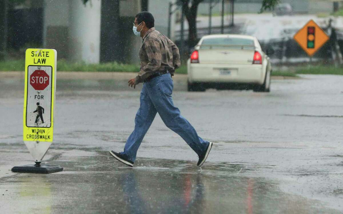 A pedestrian hurries across a cross walk as rain comes down in downtown San Antonio on Monday, May 24, 2021. Scattered showers caused some to be unprepared for the wet weather on Monday.