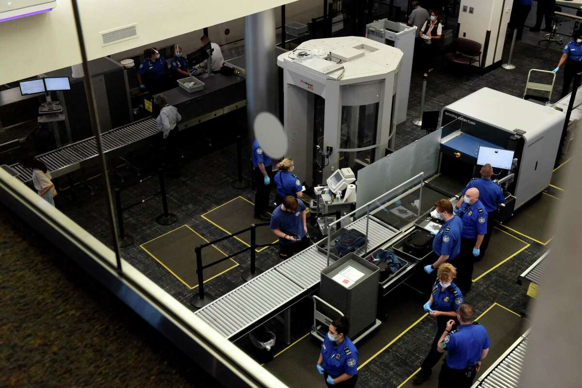 TSA personnel work in the security screening area at Albany International Airport on Thursday, May 27, 2021, in Colonie, N.Y. (Will Waldron/Times Union)