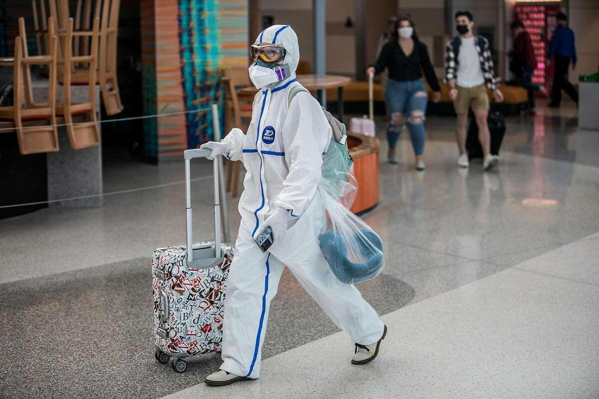 A traveler in personal protective equipment walks in Harvey Milk Terminal 1 at San Francisco International Airport in San Francisco.