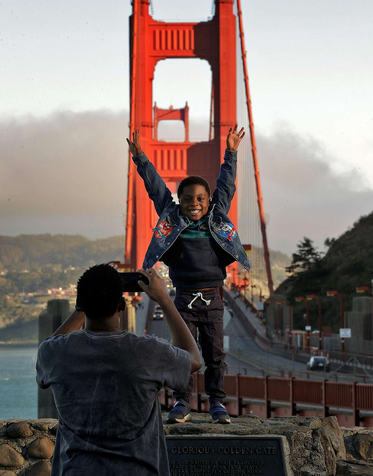 Jeramy Imhoede photographs son Jeramy, 4, in a visit to the Golden Gate Bridge with wife Angelica, all from Minneapolis, at the vista point in Sausalito. Tourism has begun to pick up again in San Francisco in advance of the travel season as the city's reopening has offered people the chance to visit with little fear of coronavirus infection.
