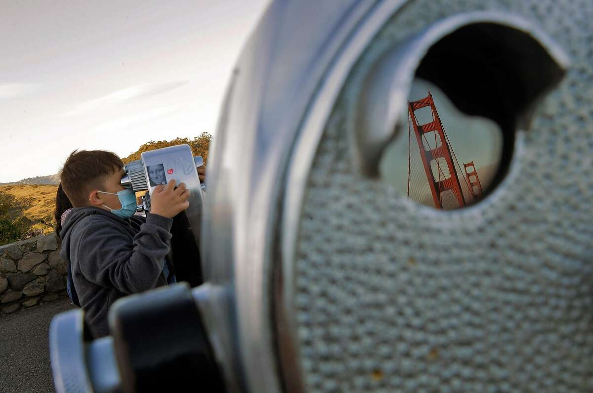 Harold Diaz, 10, of San Rafael looks out over San Francisco Bay from the vista point at the north end of the Golden Gate Bridge near Sausalito. Tourism has begun to pick up again in San Francisco in advance of the travel season.