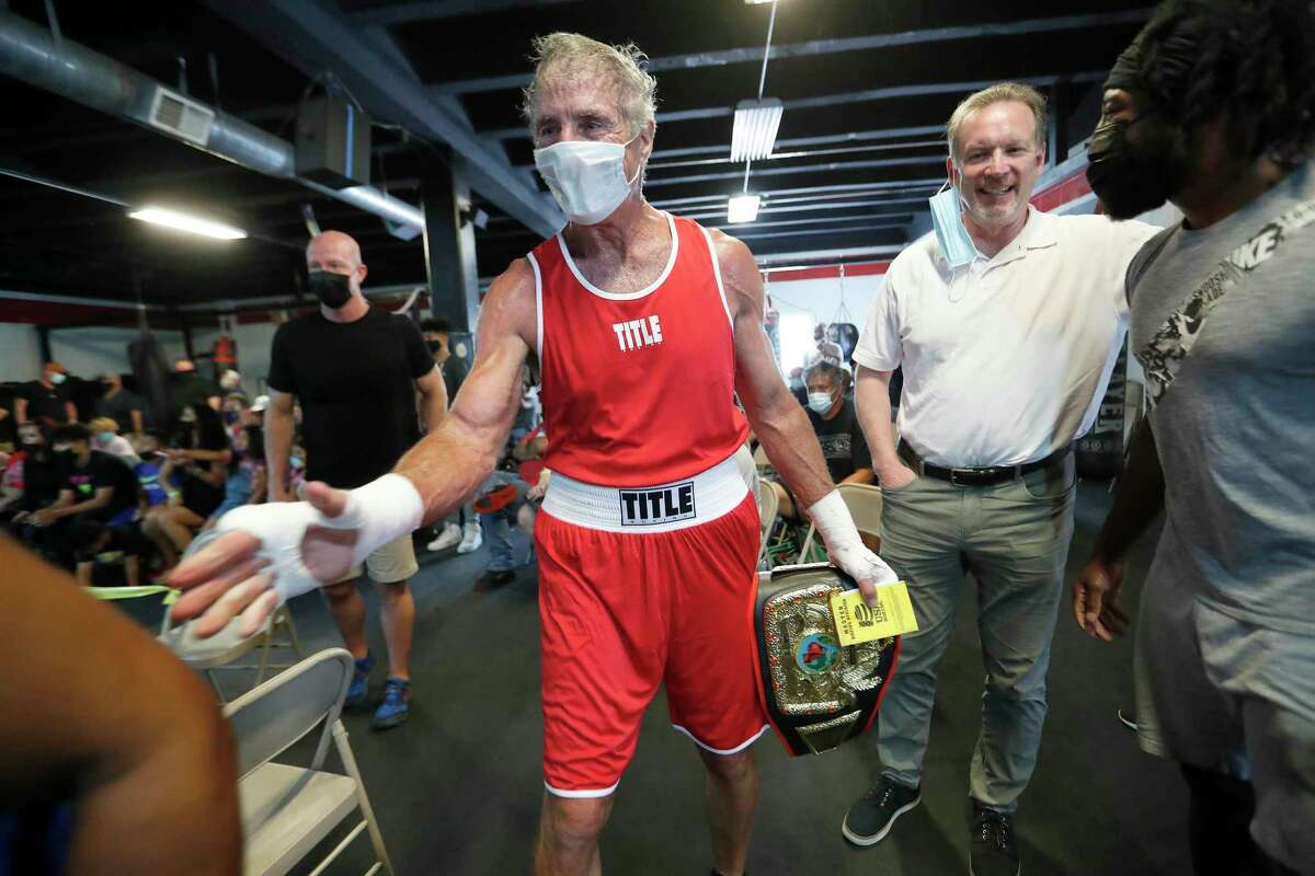 Rick Bobigian, 73, carries his belt away after winning his bout against Robert Hayward during the Texas Master's Boxing Invitational at Main Street Boxing & Muay Thai boxing gym, Saturday, May 15, 2021, in Houston.