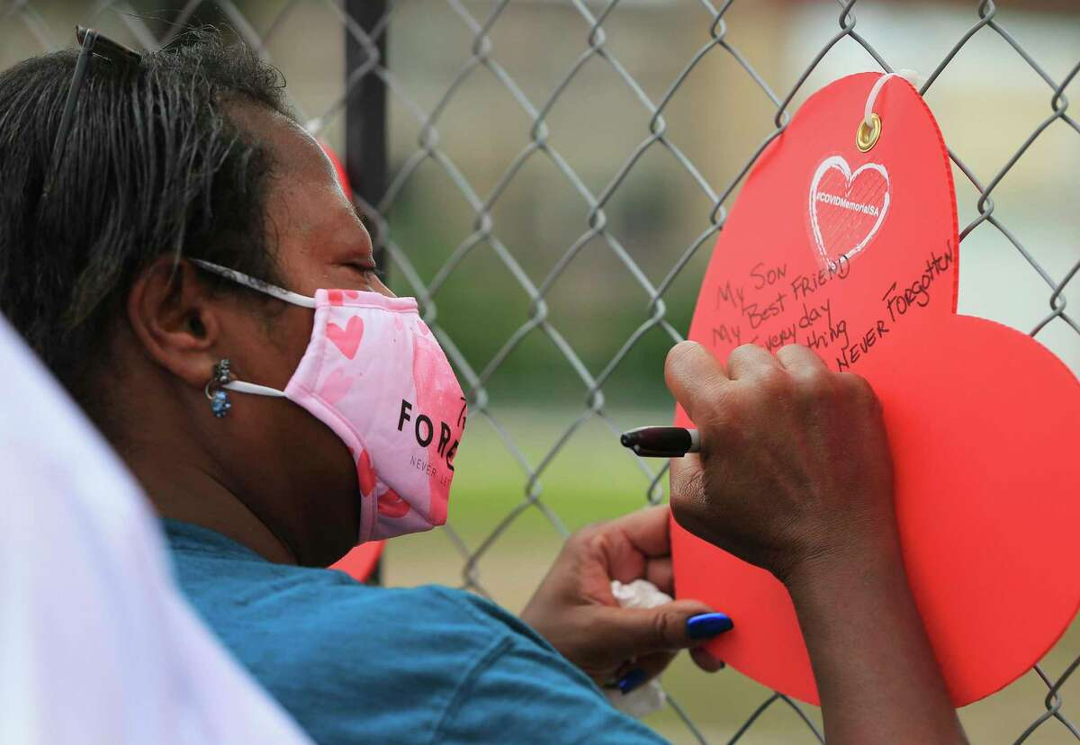 Audrey Wagstaff writes a note to honor her son, Robert, who died from Covid-19 as the City of San Antonio, Bexar County and the community honor more than 3,400 lives lost to the coronavirus with a memorial at Hemisfair near Alamo and Market Streets on Thursday, May 27, 2021.