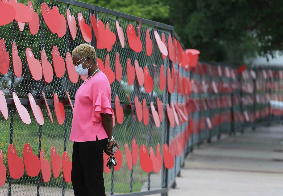 Jamelle Garner, an educator at Roosevelt High School, paused on May 27, 2021, by a wall of hearts at Hemisfair that memorialized people who have died from COVID-19.