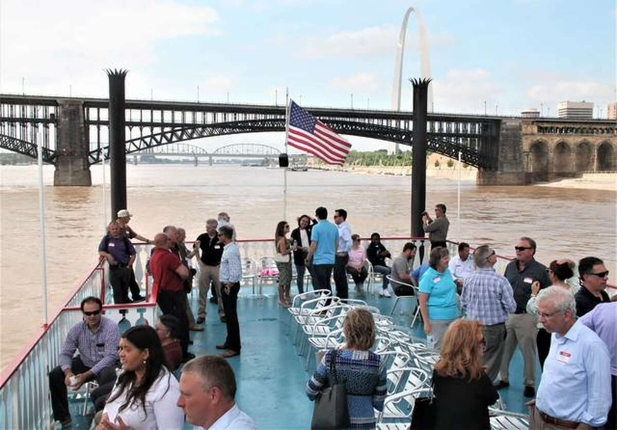 FILE - Participants of a riverboat cruise on the Tom Sawyer talk with the Eads Bridge in the background.