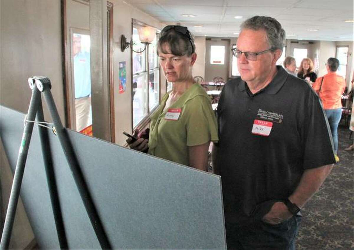 Kathy and Mike Wever from the Leadership Council Southwestern Illinois look at information about the transportation industry during a riverboat cruise Wednesday during FreightWeekSTL2021.