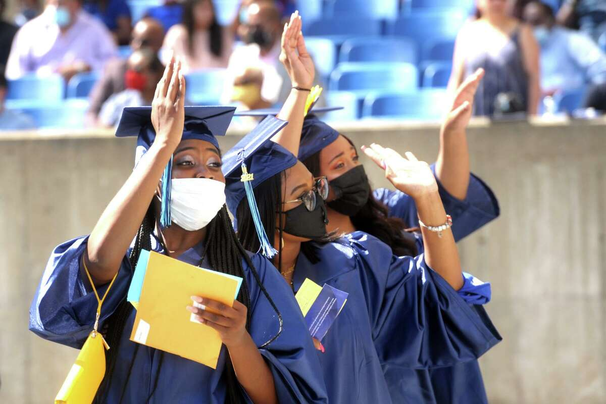 Three graduates wave to the crowd as they enter Hartford Healthcare Amphitheater for commencement of the Housatonic Community College class of 2021, in Bridgeport, Conn. May 27, 2021.