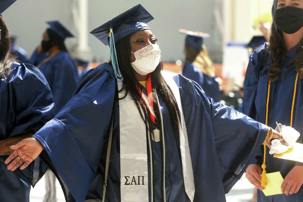 Dannette Thomas, of Bridgeport, celebrates as she and her classmates enter Hartford Healthcare Amphitheater for commencement of the Housatonic Community College class of 2021, in Bridgeport, Conn. May 27, 2021.
