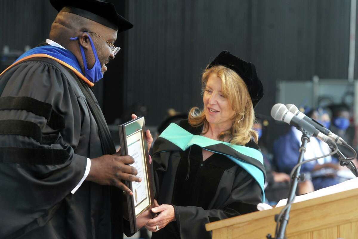 Housatonic Community College CEO Dwayne Smith presents Cindi Bigelow, President and CEO of Bigelow Tea with an honorary degree during commencement for college's class 2021 at the Hartford Health Care Amphitheater, in Bridgeport, Conn. May 27, 2021.