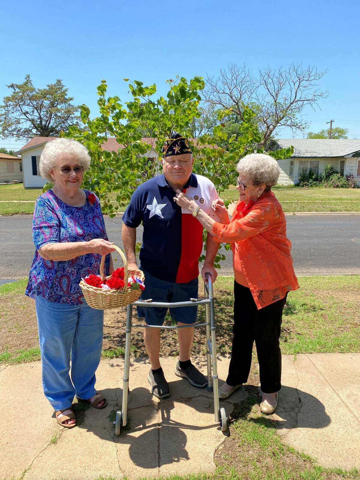 American Legion unit 260 President Theta Vaughan (left) holds a basket of poppies as Sgt. At Arms Betty Dykes pins a flower on the collar of veteran Ralph Langley.
