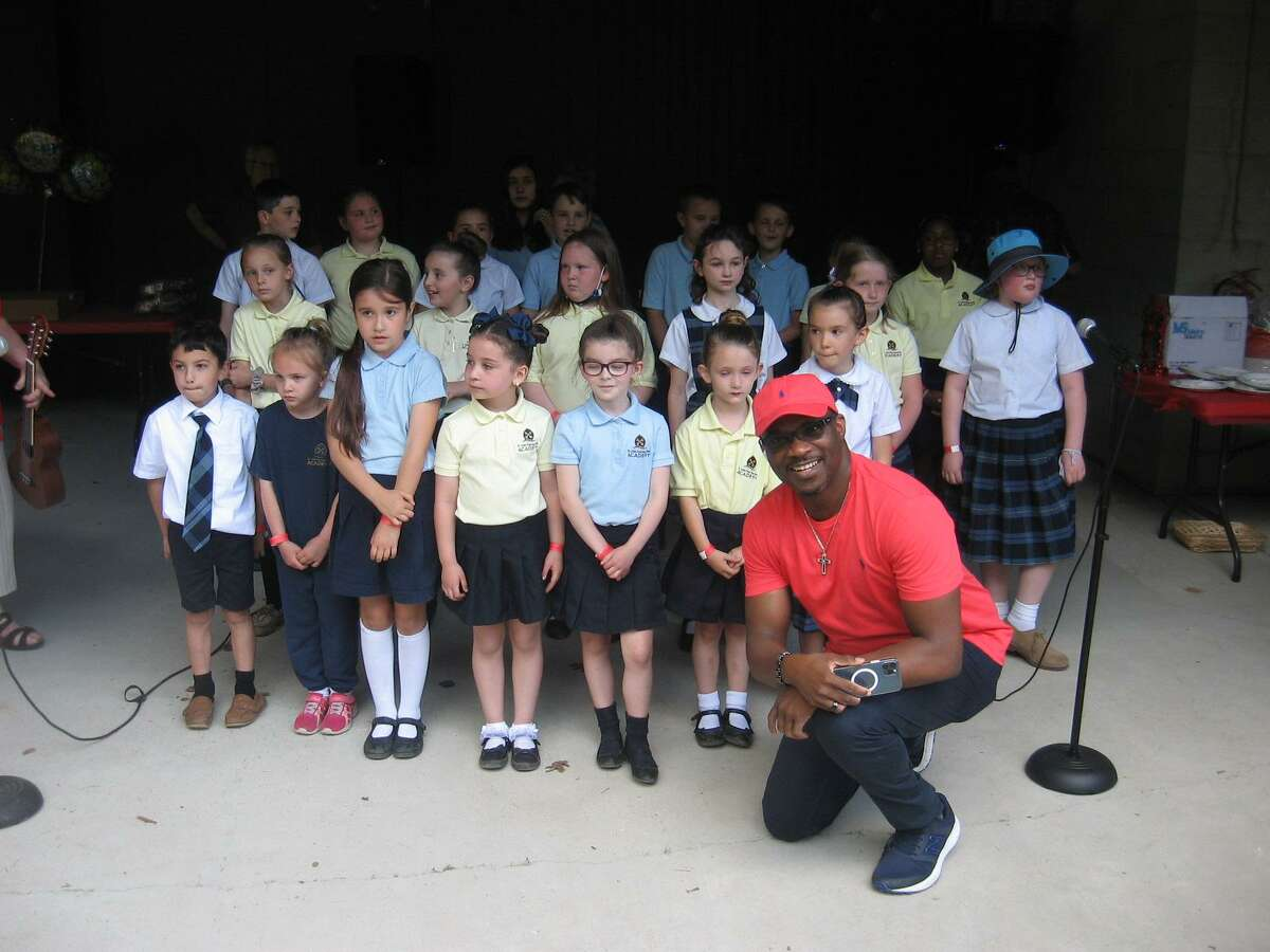 St. John Paul the Great Academy threw an anniversary party for the Rev. Emmanuel Ihemedu at Action Wildlife pavilion in Goshen. Above, he poses with the children's choir.