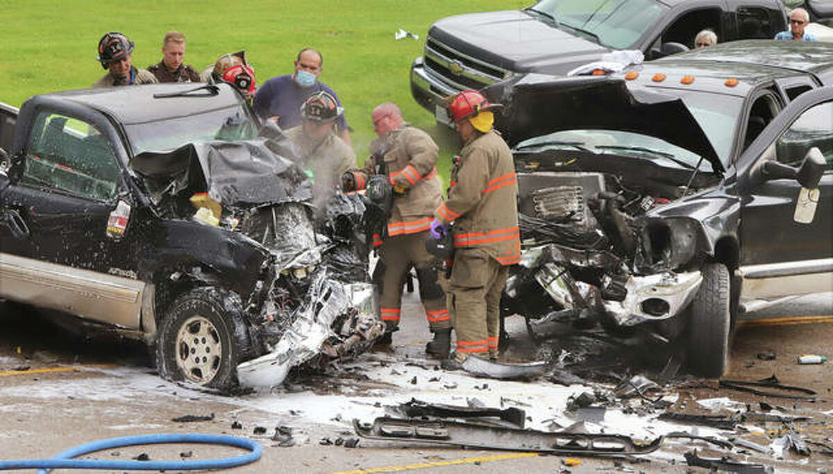 Godfrey firefighters use an hydraulic rescue tool on a full size Chevrolet pickup truck, left, Thursday to free a driver trapped after a head-on crash about 12:25 p.m. on Delmar Avenue at Emma Lane in Godfrey. The Chevrolet crashed with a Dodge Ram pickup truck. Both drivers were transported to area hospitals.