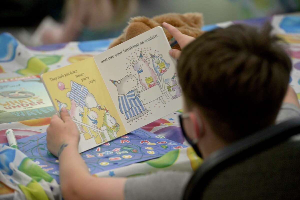 A boy reads along with Hospitalist Dr Beth Natt from the Connecticut Children's Medical Center. Natt was reading
