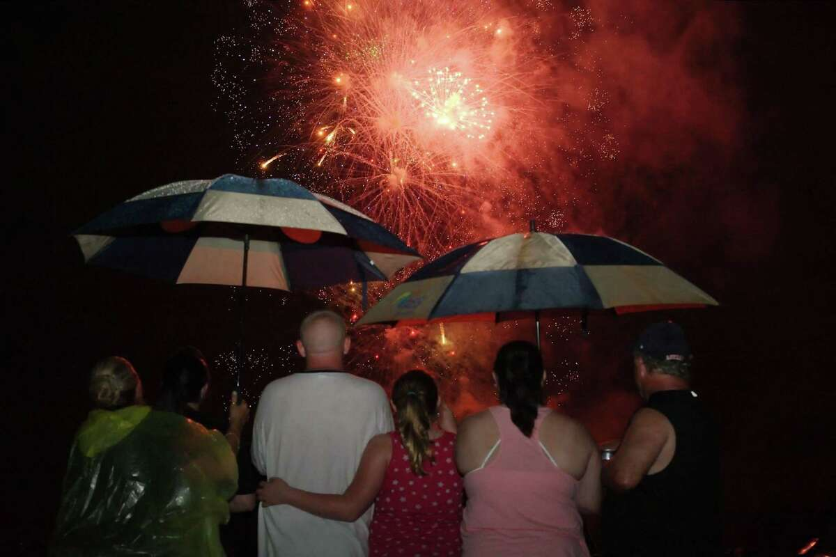 A family doesn't let rain stop their enjoyment of a previous July Fourth fireworks display by the city of Pasadena. The display planned for 2021 will include food trucks.