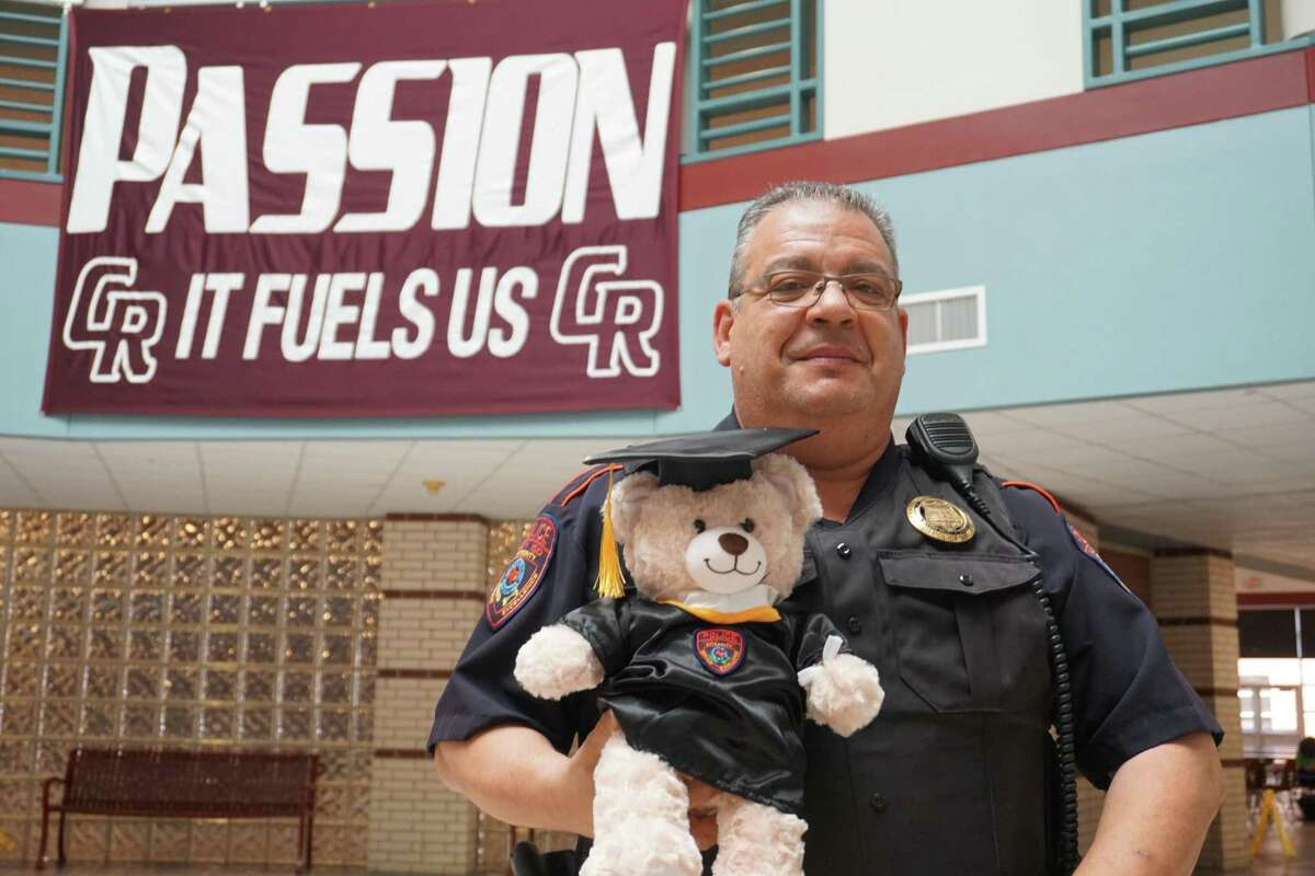 Luis Santiago, a Katy Independent School District police officer, poses at Cinco Ranch High School in Katy with a Teddy Grad bear he created to give graduating students with disabilities to let them know that police officers are friends who can be trusted.