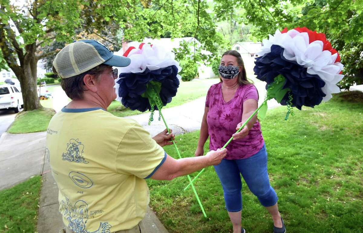 Marlene Sanchez (left) purchases red, white and blue tissue paper flowers from Sandy Ross in Milford on May 22, 2021.
