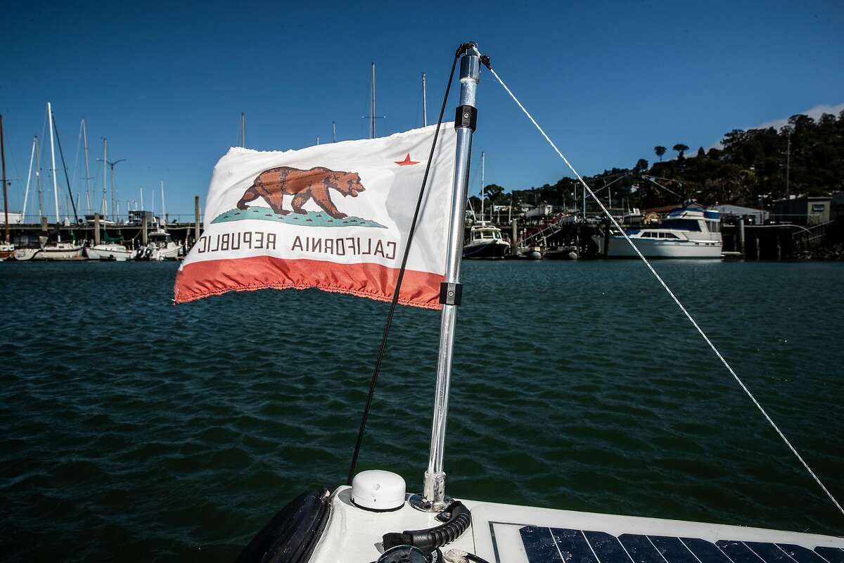 A California state flag is waves against the wind on Cyril Derreumaux's custom ocean kayak in Sausalito, Calif., Wednesday, May 5, 2021. The Marin-based French-American adventurer is set to embark on a 70-day solo unsupported kayak trip from San Francisco to Honolulu, Hawaii at the end of May.