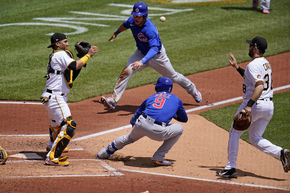 Will Craig tosses the ball to catcher Michael Perez after chasing Chicago batter Javier Baez to the plate as Willson Contreras prepares to slide. Baez reversed course and wound up on second after an errant throw.