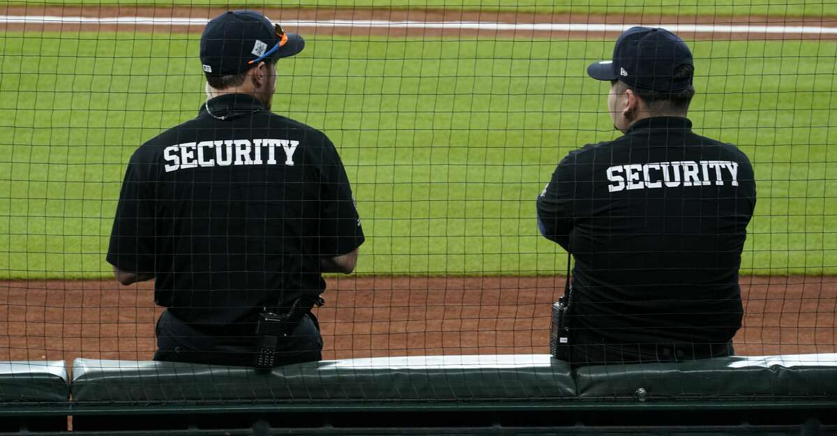 Security guards sit against protective netting before the Houston Astros and Detroit Tigers MLB game at Minute Maid Park Monday, Aug. 19, 2019, in Houston. The Astros extended the netting inside Minute Maid Park in an effort to better protect fans from foul balls.