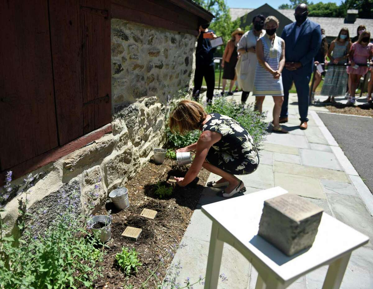 Sacred Heart Greenwich teacher Kelly Bridges places a stone at the Witness Stones Memorial unveiling ceremony at the Bush-Holley House in the Cos Cob section of Greenwich, Conn. Thursday, May 27, 2021. A group of students and educators from Sacred Heart Greenwich and Greenwich Academy have been researching the lives of four enslaved laborers for the past two years, to bring them out of the historical shadows, and four stones with their names on them were laid next to the building where they were believed to have lived and slept.