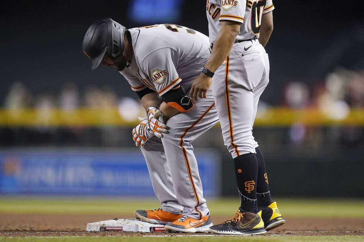 An injured San Francisco Giants' Darin Ruf pauses at first base during the sixth inning of a baseball game against the Arizona Diamondbacks Wednesday, May 26, 2021, in Phoenix. (AP Photo/Ross D. Franklin)