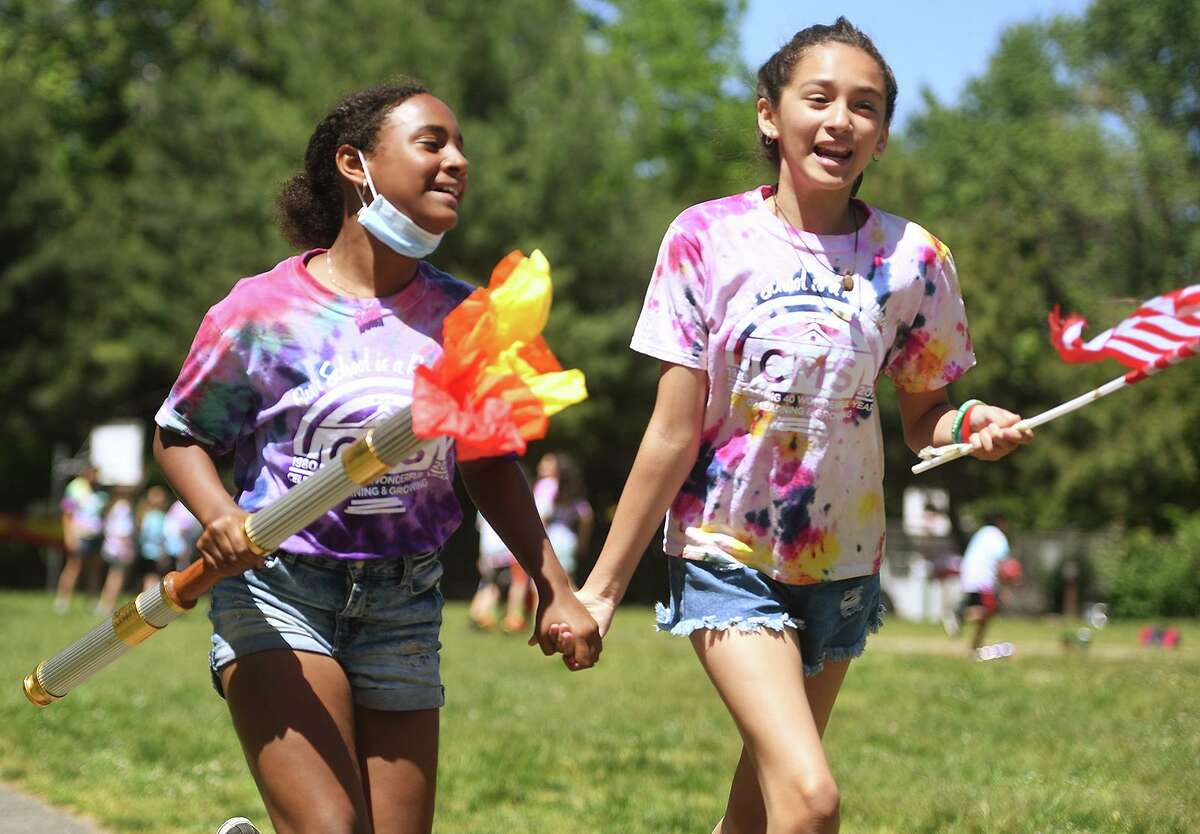 Fifth graders Rosairy Ortega, left, and Isabella Suarez, both 10, run hand in hand as they participate in the Olympic Torch Run at Columbus Magnet School in Norwalk on Thursday. Below, Fourth grader Tarek Bennani, 9, shows his running form as he carries the torch