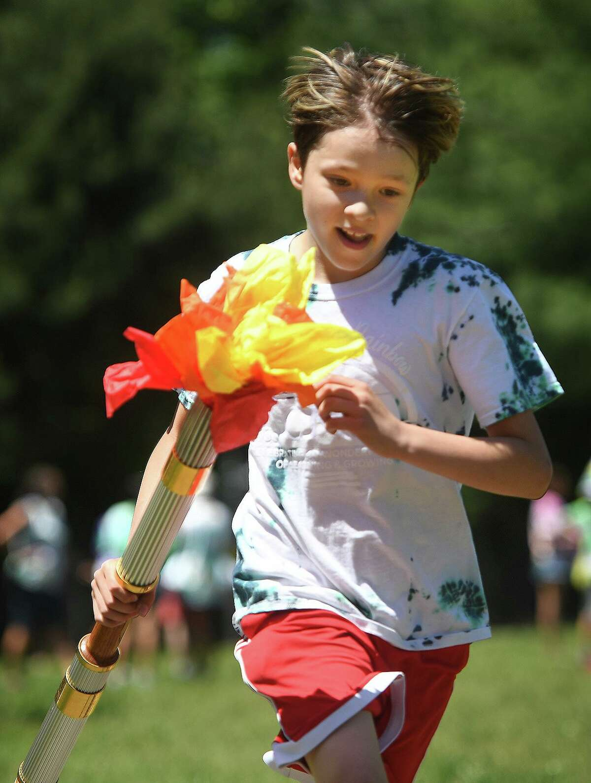 Fourth grader Tarek Bennani, 9, shows his running form as he carries the torch in the Olympic Torch Run at Columbus Magnet School in Norwalk, Conn. on Thursday, May 27, 2021.
