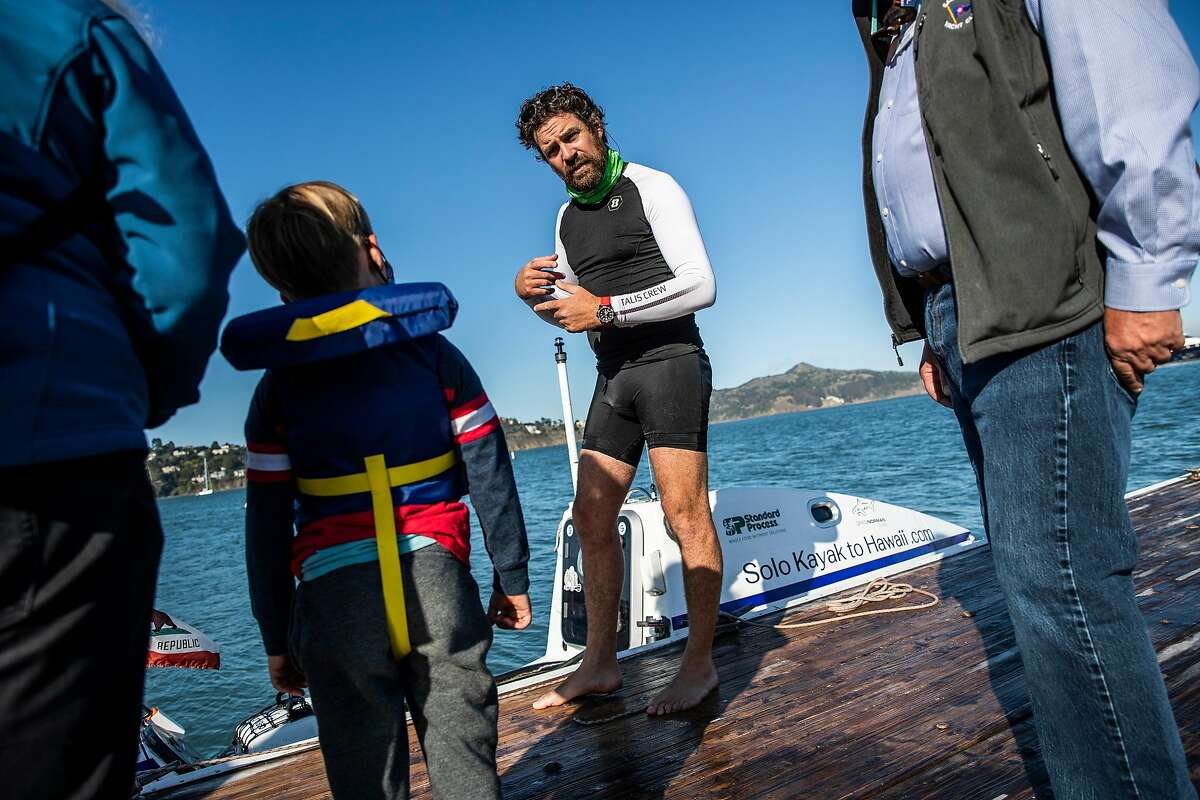 Cyril Derreumaux (center), who is about to take his kayak on a two-mouth journey to Hawaii, answers a question from 6-year-old Micah Chavez at the Sausalito Yacht Club this month.