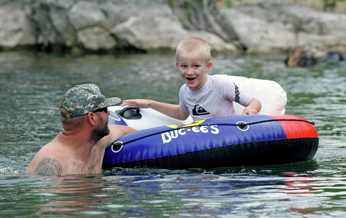 Steven Wilden navigates his son Waylon away from rapids on the Guadalupe River upsream from New Braunfels on May 5, 2020. The pandemic was a 'disaster' for the river tourism industry, New Braunfels' mayor said.