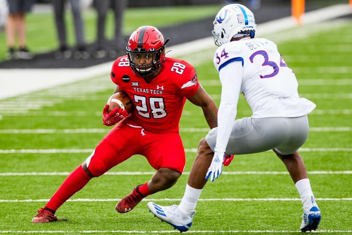 LUBBOCK, TEXAS - DECEMBER 05: Running back Tahj Brooks #28 of the Texas Tech Red Raiders runs the ball against safety Nate Betts #34 of the Kansas Jayhawks during the first half of the college football game at Jones AT&T Stadium on December 05, 2020 in Lubbock, Texas. (Photo by John E. Moore III/Getty Images)