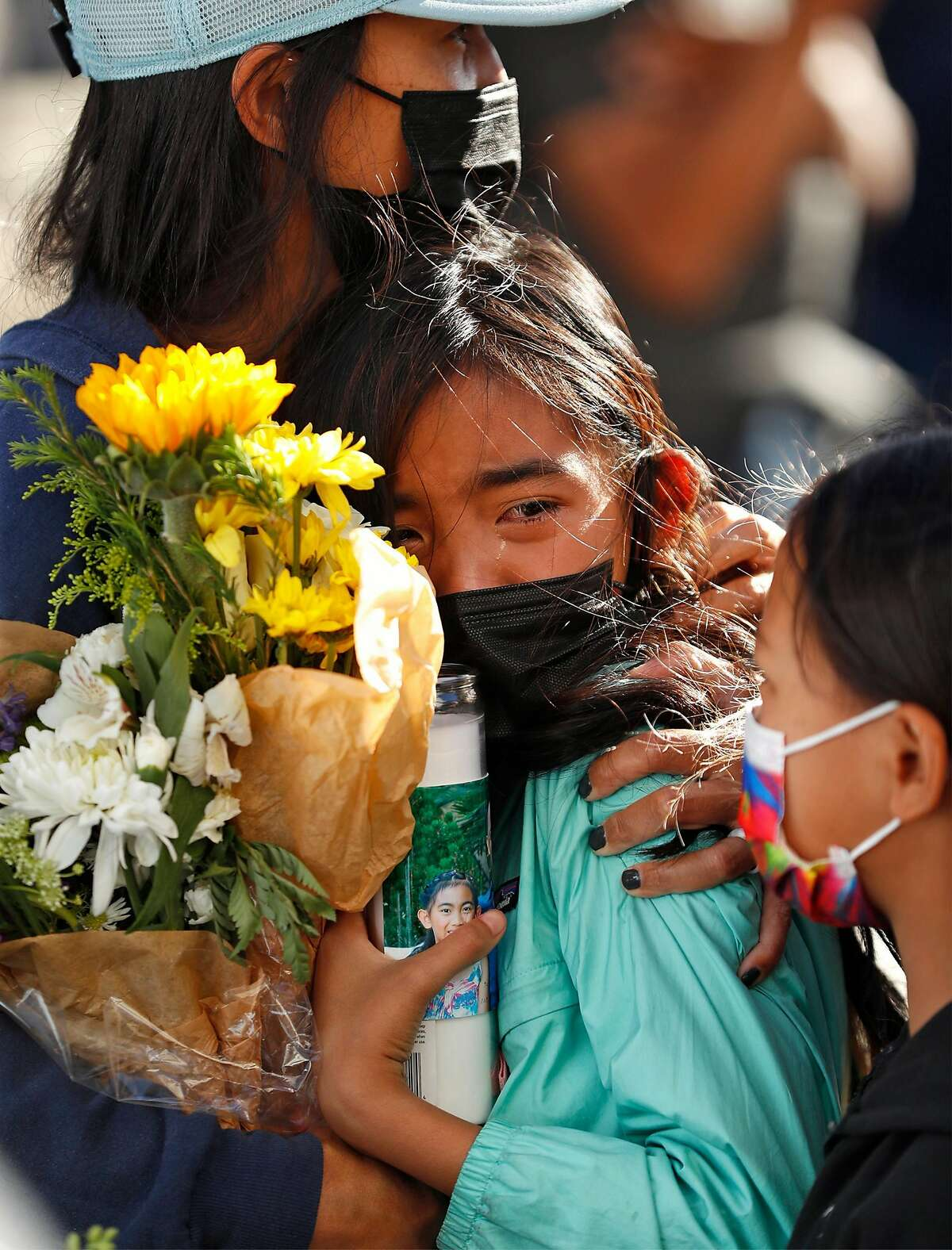 Avery Megia, the daughter of victim Paul Megia sheds a tear as she is comforted during a public vigil on Thursday, May 27, 2021, at San Jose City Hall in wake of Wednesday's mass shooting that claimed 9 lives at Valley Transportation Authority's maintenance yard in San Jose, Calif..
