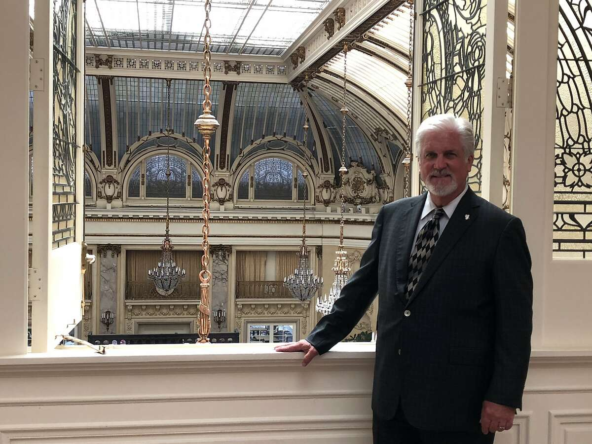 Clifton Clark, general manager of the Palace Hotel, is overseeing the reopening of the historic facility, including the elegant Garden Court, shown behind him.
