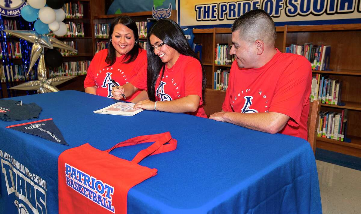Cigarroa's Kassy Martinez is joined by her parents Claudia Martinez and Javier Martinez as she signs her National Letter of Intent to play basketball at Arlington Baptist University on Thursday, May 27, 2021 at the Cigarroa High School Library.