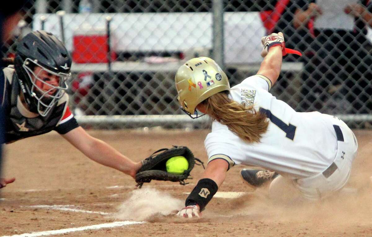 Notre Dame of Fairfield's MacQuarrie Stone-Folmar (7) reaches home plate to score as Masuk's Isabel Viglione (13) attempts the tag during SWC championship girls softball game action at DeLuca Field in Stratford, Conn., on Thursday May 27, 2021.