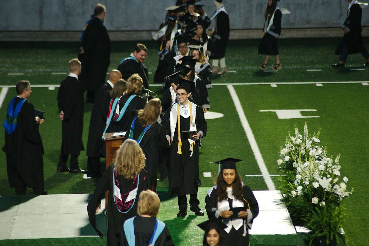 Shadow Creek High School graduates walk across the stage to receive their diplomas during graduation at Alvin ISD Freedom Field for graduation Thursday, May 27.