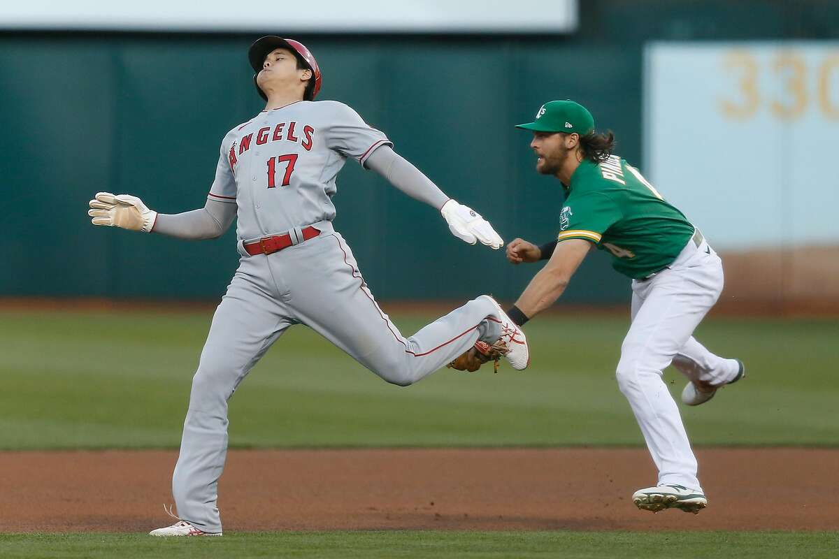 OAKLAND, CALIFORNIA - MAY 27: Base runner Shohei Ohtani #17 of the Los Angeles Angels is tagged out on his way to second base by Chad Pinder #4 of the Oakland Athletics in the top of the fourth inning at RingCentral Coliseum on May 27, 2021 in Oakland, California. (Photo by Lachlan Cunningham/Getty Images)