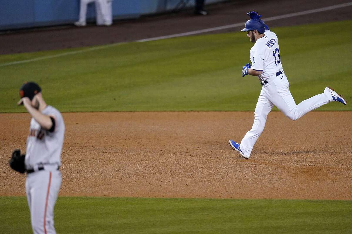 Los Angeles Dodgers' Max Muncy, right, heads to third after hitting a solo home run as San Francisco Giants starting pitcher Alex Wood stands on the mound during the sixth inning of a baseball game Thursday, May 27, 2021, in Los Angeles. (AP Photo/Mark J. Terrill)